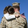 soldier holds girl with flag