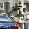 young adult unpacks car with father