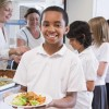 smiling boy with plate leaves cafeteria line