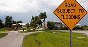 Street sign cautions, road subject to flooding
