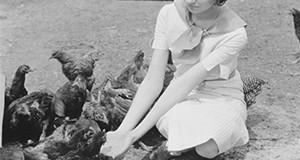 Young woman feeding chickens. Source: Smather's Archives.