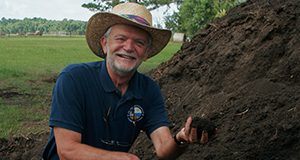 UF/IFAS professor George O'Connor holds up a handful from a pile of biosolids with forage range in the background.