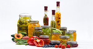 Canned food.  Fruits and vegetables, cans, mason jars, bottles.  July 2010 IFAS Extension Calendar image.  UF/IFAS Photo by Tom Wright.