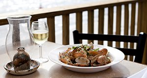 A plate of Sunray Venus clams set at an outdoor table overlooking the ocean.