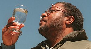 A man examines a glass of water in the sunlight.