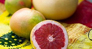 A photo of a halved red grapefruit and other whole grapefruits in the background, all on a Florida citrus bag.