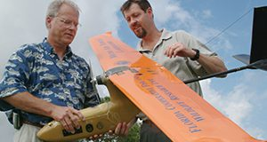 Franklin Percival, left, and Peter Ifju, professors at the University of Florida, examine a small plane that can photograph and monitor wildlife and their habitats - Oct. 19, 2004. Controlled by its own on-board computer, the plane stores and downlinks high-quality video and flight data to researchers on the ground. The unmanned aerial vehicle, or UAV, is being developed by UF's College of Engineering in cooperation with UF's Institute of Food and Agricultural Sciences. (AP photo/University of Florida/IFAS/Marisol Amador)