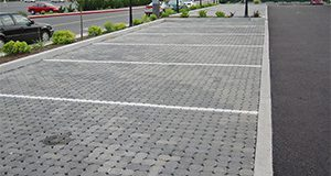Newly installed PICP parking stalls as part of a commercial installation. Note the curb separating landscaping and directing runoff away from the pavement surface.