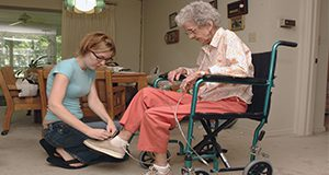Elderly person receiving assistance from a caregiver with everyday tasks. UF/IFAS Photo by Marisol Amador.