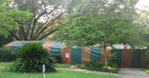 A modest Florida ranch house with dogwoods, oak trees, and a largec cycad in the yard. House is completely covered by a green and orange striped tent with a warning signed pinned near the front walkway indicating fumigation..