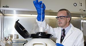 A photo showing a person wearing a lab coat and nitrile gloves inserting a sample into a cryogenic storage container.
