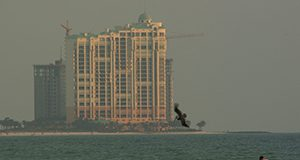 A photo of a multistory beachfront hotel or condominium at sunset with construction cranes, ocean in the foreground.