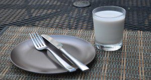 A metal plate with fork and knife, next to a glass of almond milk. Credit: Lincoln Zotarelli, UF/IFAS